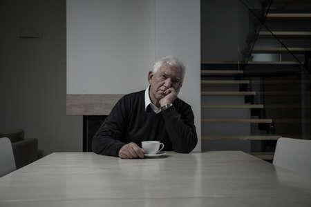 hombre tomando cafe: Hombre mayor triste que se sienta en la mesa