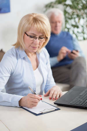 outgoings: Middle-aged woman summarizing all of the incomes and outgoes Stock Photo
