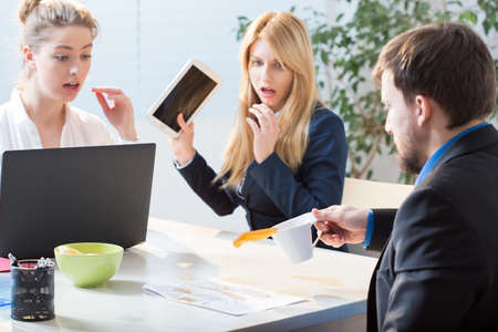 destroying: Man spilling tea on documents at work Stock Photo