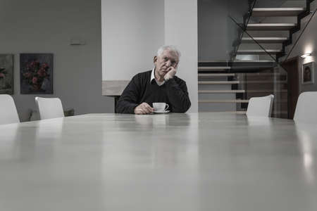 Lonely senior man being alone at big house Stock Photo