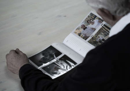 family memories: Lonely elder man looking into family photo album Stock Photo