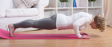 salutation: Aged exercising woman during yoga sun salutation Stock Photo