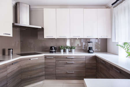 kitchen: Cozy beige kitchen interior with wooden cupboards