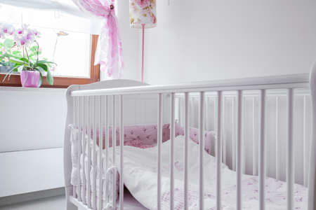 nursery: Close-up of white crib in nursery room Stock Photo