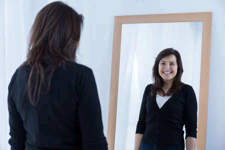 woman mirror: Reflection of girl wearing a fake smile