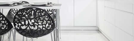 table and chairs: Black elegant chairs in white kitchen interior
