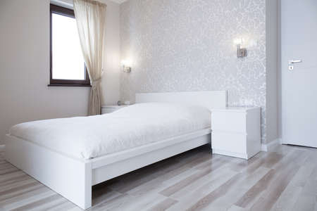 White bed in bright bedroom in apartment