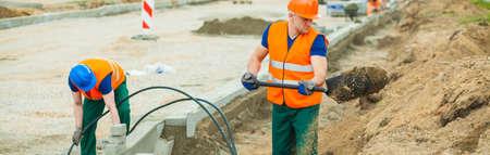 Contruction werknemers graven in de elektrische kabels Stockfoto