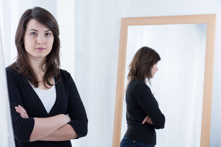mirror frame: Woman in black pullover standing with crossed arms