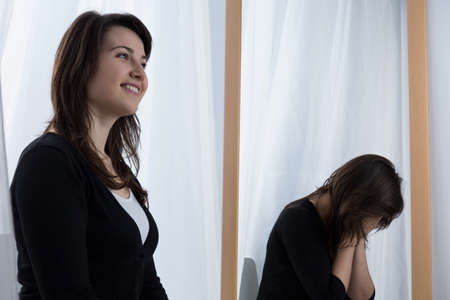 dissimulation: Depressed young woman wearing a fake smile
