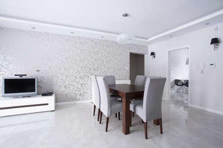 luminoso interior con paredes de plata y mesa de madera