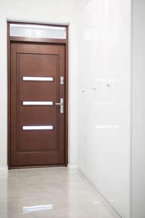 white door: Wooden door in white hall in apartment Stock Photo