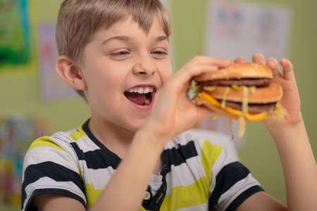 greasy: Happy hungry boy trying big greasy burger