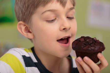 eating pastry: Hungry greedy child eating delicious chocolate cupcake