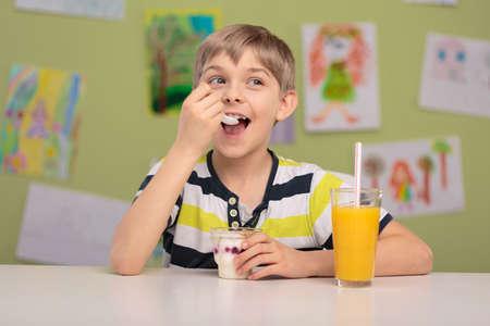 botanas: Niño feliz comiendo merienda saludable y beber jugo de naranja Foto de archivo