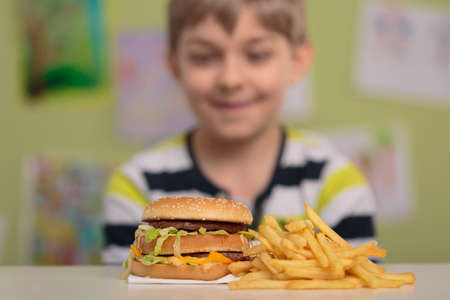 junks: Hungry boy looking at big burger and chips