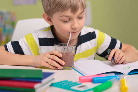Smart kid doing homework and drinking cocoa