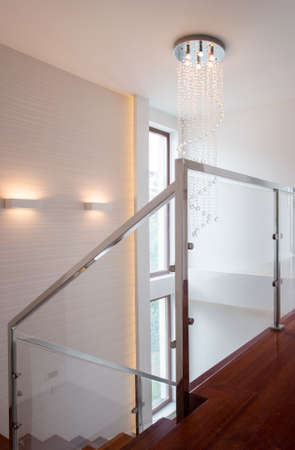 anteroom: Stylish project of wooden stairs with glass rails
