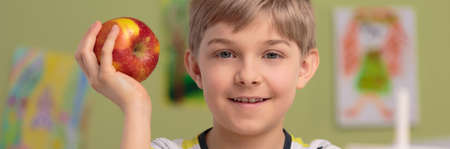 panoramic: Panoramic photo of smiling boy with red apple