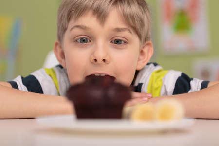 pastel de chocolate: Muchacho sorprendido codicioso y sabrosa muffin de chocolate