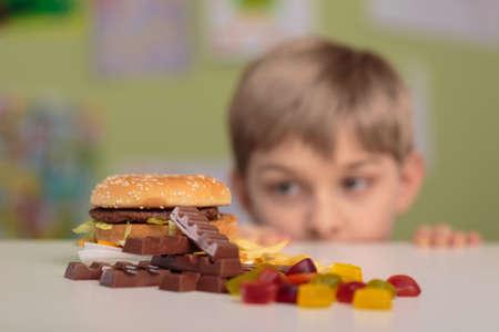 botanas: Pequeño niño codicioso mirando sabrosos aperitivos poco saludables