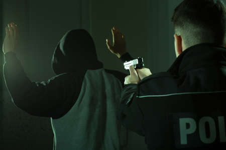 crook: Image of a police officer keeping gun on a crook