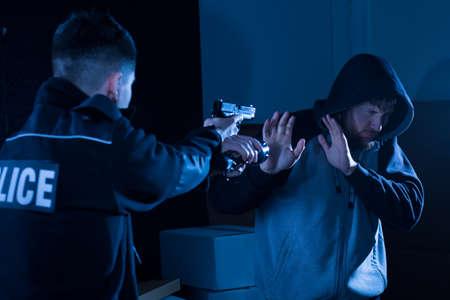 criminal defense: Image of criminal with gun aiming at him giving up