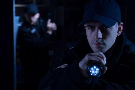 Close-up van de knappe politieman met zaklamp