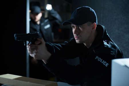 hombre disparando: Retrato de un policía atractiva que apunta el arma durante la acción