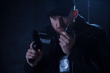 inform: Image of a serious policeman holding radio and gun Stock Photo