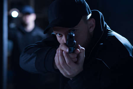 man holding gun: Image of a focused policeman aiming gun during intervention Stock Photo