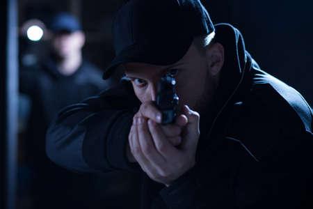 pistolas: Imagen de un policía enfocada apunta el arma durante la intervención