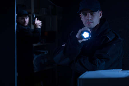 flashlight: Photo of a young policeman holding flashlight during action