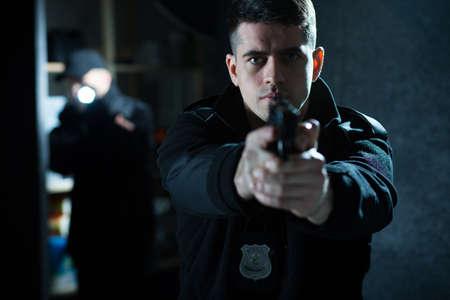 Afbeelding van een zelfverzekerde knappe politieagent houdt een pistool Stockfoto
