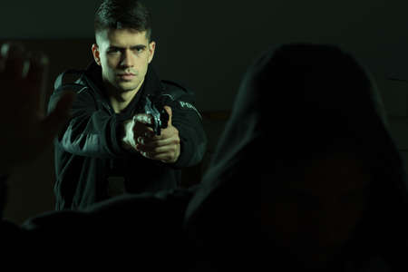 hombre disparando: Imagen de un policía confía guapo apuntando la pistola en penal Foto de archivo