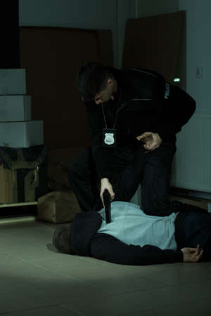 overpowering: Image of a strong cop overpowering a lawbreaker