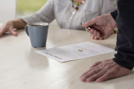 persuading: Husband waiting for his wife to sign the divorce decree Stock Photo