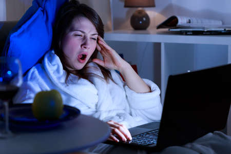 girls night: Exhausted woman yawing late at night in front of computer Stock Photo