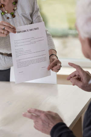unmarried: Mujer que muestra los papeles del divorcio a su marido