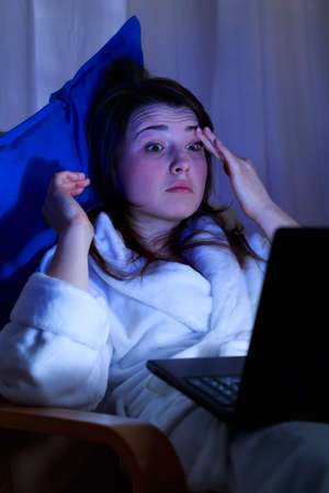 overuse: Tired young woman sitting late at night with laptop
