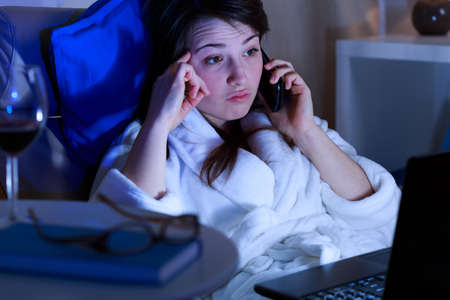 Tired girl talking on the phone late at night Stock Photo