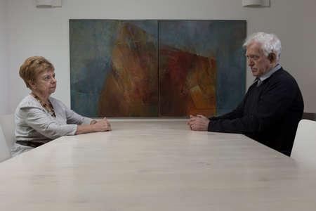decission: Moglie e marito su entrambi i lati del tavolo Archivio Fotografico