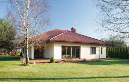 casa de campo: Fachada de la casa unifamiliar en día soleado