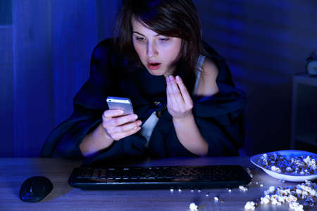 untidy text: Shocked young woman reading text message on her phone Stock Photo