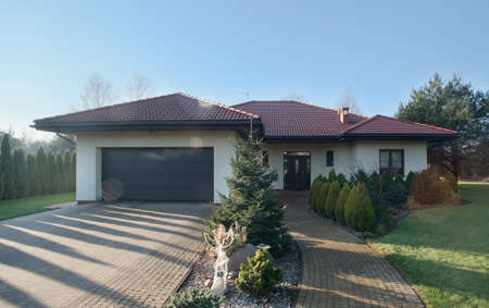 Exterior of detached house with garden on sunny day Standard-Bild