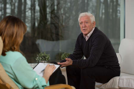 retiree: Retiree talking about his problems during psychotherapy session Stock Photo