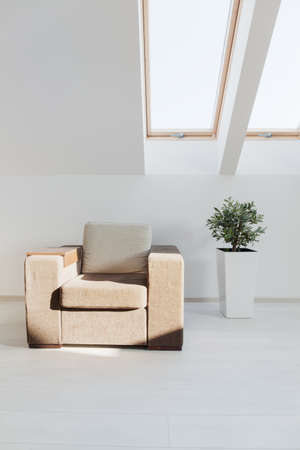 sunlit: Simple beige armchair in all-white furnished attic living room Stock Photo