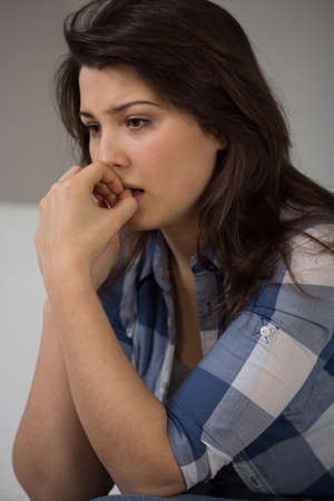 neurosis: Portrait of young depressed woman biting her nails Stock Photo