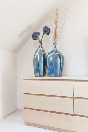 chest of drawers: Two decorative blue vases on the chest of drawers