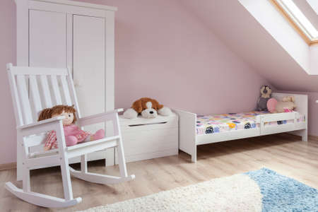 niñas pequeñas: Mecedora en la habitación lindo para la niña Foto de archivo
